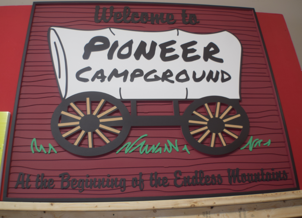 HDU sign with a 3D graphic of old-fashioned wagon and text that reads: Welcome to PIONEER CAMPGROUND At the Beginning of the Endless Mountains
