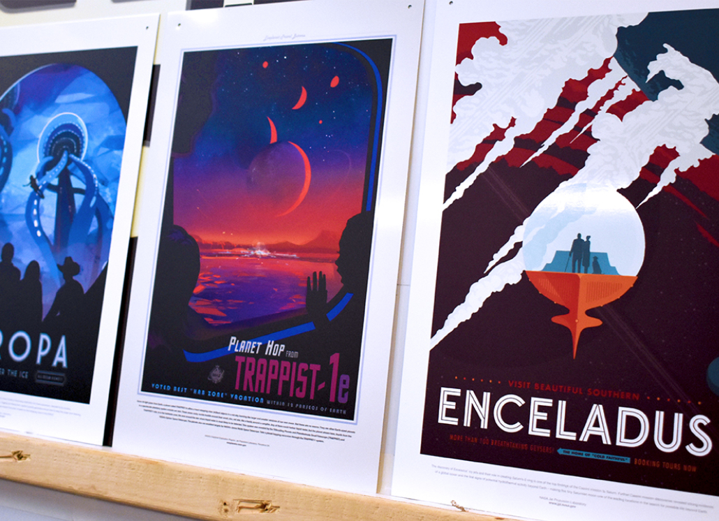 Three painted aluminum signs with graphics of planets and moons and text that reads: PLANET HOP FROM TRAPPIST-1e VISIT BEAUTIFUL SOUTHERN ENCELADUS